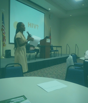 Shekinah Thomas, CEO, speaking at conference, HIV on slide behind on a large screen behind her