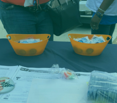 Two women standing in front information table with two large bowls with condoms