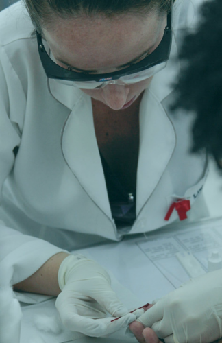 Doctor with safety glasses drawing blood