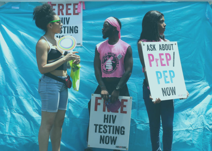 Diverse AIDS/HIV volunteers holding signs for FREE testing